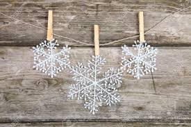 christmas decorations snowflakes hanging over wooden background