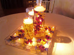 white candle and white flower also water inside round glass holder