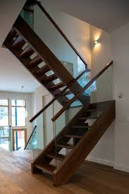 walnut freestanding stairs with open risers and glass railings by
