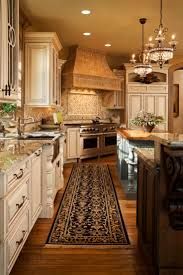 best ideas about tuscan kitchens pinterest kitchen twin chandeliers hang over one two islands this richly detailed kitchen natural hardwood