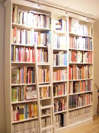 high white wooden books shelves plus white wooden ladder placed on