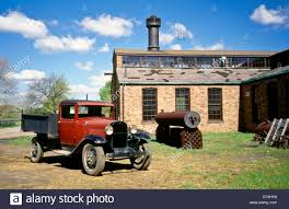 Antique Ford Truck Models - old red ford model a pick up truck next to an old factory