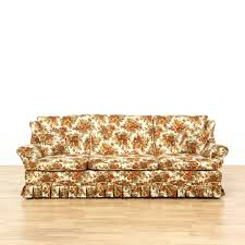 Orange Pillows For Sofa by This Sofa Is Upholstered In An Orange Floral Pattern This