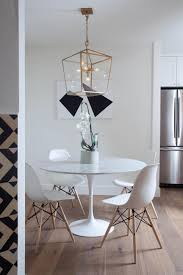 white eames style dining chairs surround the contemporary round