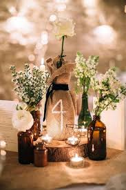 picture of centerpiece with small bottles with flowers and