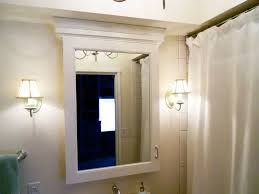 bathroom with wall sconces and medicine cabinet with mirror