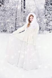 woman in white snow suit standing on a snow covered ground behind