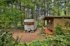 a little cabin and trailer in the whidbey island woods curbed