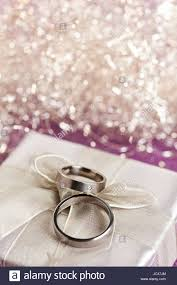 silver boxes with bows on top pair of wedding rings on top of silver gift box with bow
