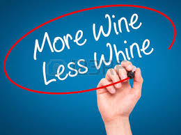 man hand writing more wine less whine with black marker on visual