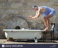man in retro swimsuit jumps to the outdoor bathtub stock photo