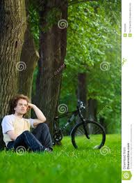 young man siting under the tree near his bycicle royalty free