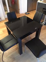 next black gloss extending table and matching chairs in