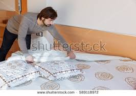 bed making man beard making bed stock photo 589118972 shutterstock