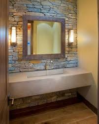 bathroom stone wall with wall lamps and concrete sink plus wooden