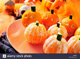 a pile of mandarines ornamented as pumpkins with scary