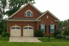 garage door replacement 10 tips for making the right choice the arched shape of these garage doors window openings and the division of the windows with square grilles mimic the design of the arched windows to the