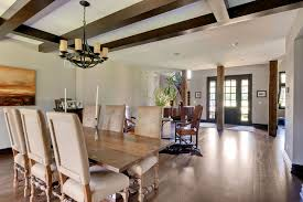 dining room with wooden ceiling beams and view of solid wood entry