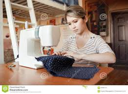 young woman sewing with sew machine at home while sitting by her