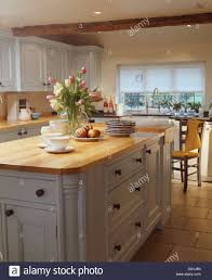 wooden worktop on fitted white unit below open white shelves in