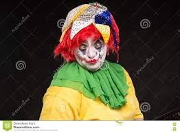 halloween scary background green scary clown joker with a smile and red hair on a black backgroun