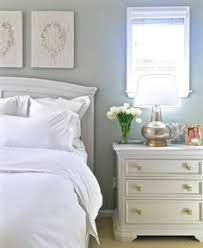 the guest room with walls painted a silver sage color and art