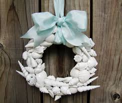 decorating white seashell wreath with blue ribbon for charming
