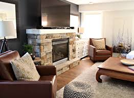 family room with tv on mantel above stone fireplace with 2 leather