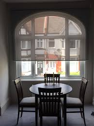 sunscreen roller blind to arched window for a dining room in