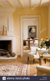 cream upholstered armchair beside fireplace in french country