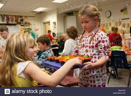 three kids sitting at table in classroom eating halloween