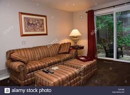 a cosy family room with a couch sofa with two ottomans and an