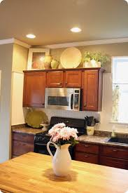 above kitchen cabinet decor ideas how to decorate above kitchen cabinets from thrifty decor