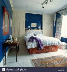 blue bedroom with grey carpet and wall cupboards stock photo