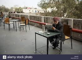 a man reads a newspaper on the roof terrace of the indian coffee