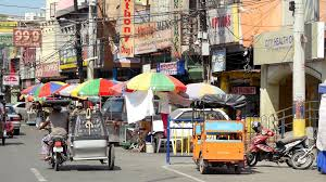philippine tricycle street view of traffic with tricycles and motorbikes passing by