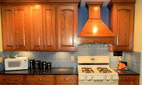 rustic kitchen cabinet and wooden range hood also grey subway tile