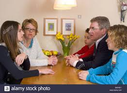 teenagers talking with adults at family meeting at table stock