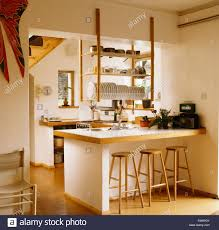 breakfast bar wooden stools at breakfast bar below hanging wooden shelves in