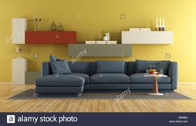 modern living room with blue sofa and colorful wall unit on yellow