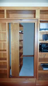 white built in bedroom shelving units over green murphy bed mini