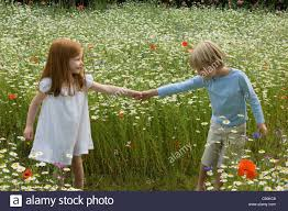 children walking in field of flowers stock photo royalty free