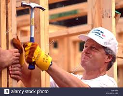 president bill clinton works to frame a house during a habitat for