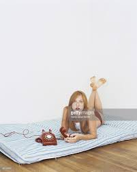 woman lying on mattress on floor with rotary phone stock photo