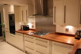 cream gloss kitchen stainless steel splash back and walnut work