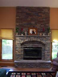 master stone fire place wood shelves tv wall mount dark wooden