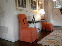 dining room with orange chairs and metal chandelier also