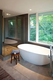 bathroom white acrylic freestanding tub and rounded brown wooden