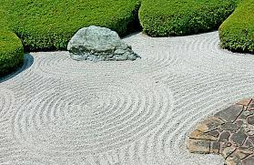 outdoors beautiful rock garden with green plants and raked
