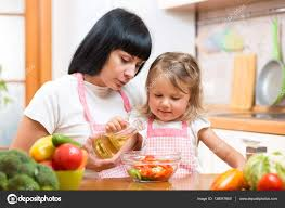 mother teaching child daughter making salad in kitchen cooking